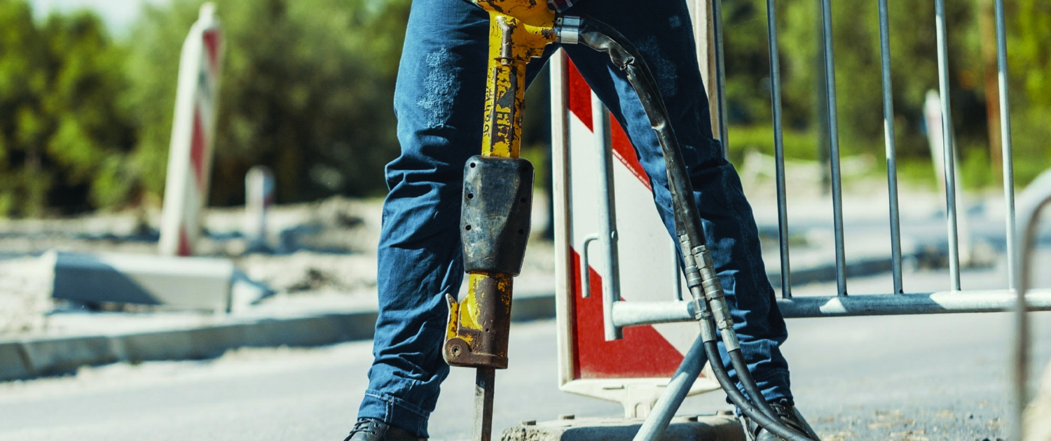 Construction worker drilling on a jobsite