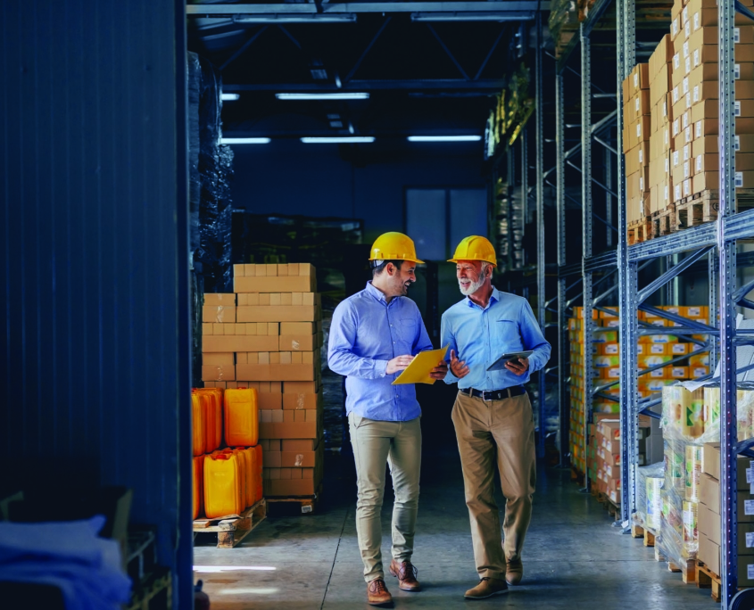 Two workers talking and walking in a warehouse