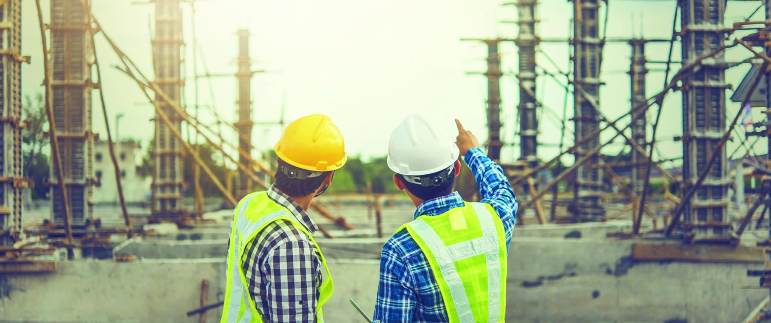Two construction workers looking at a construction jobsite