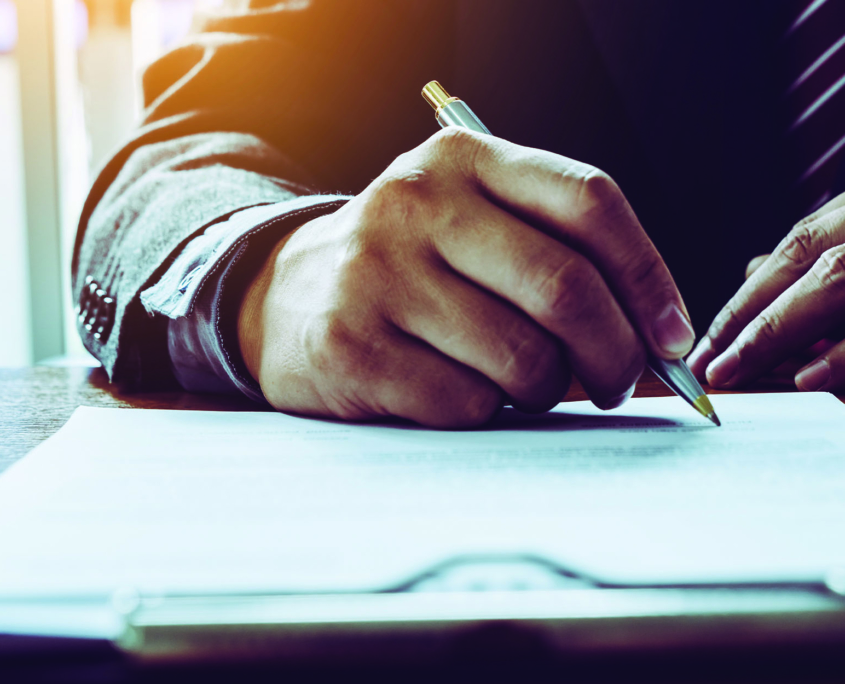 Business person signing a document