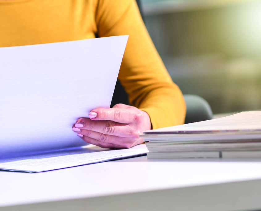 Employee looking at a file on her desk