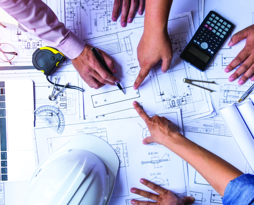 Team looking and pointing at construction layouts